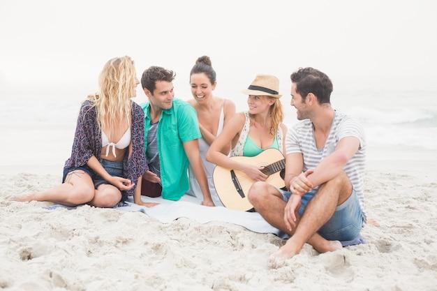 Gruppe von freunden sitzen am strand mit gitarre