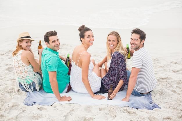 Gruppe von freunden sitzen nebeneinander am strand mit bierflaschen