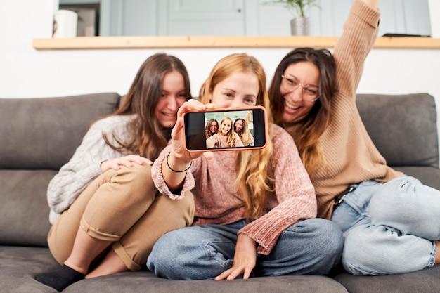 Gruppe von freundinnen auf dem sofa zu hause, die ein selfie nehmen