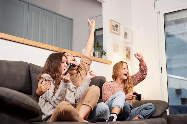 Gruppe von freundinnen, die auf sofa im wohnzimmer sitzen und videospiele zu hause spielen
