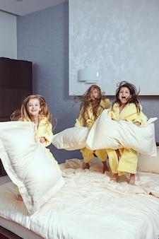 Gruppe von freundinnen, die gute zeit auf dem bett nehmen. glückliche lachende kindermädchen, die auf weißem bett im schlafzimmer spielen.