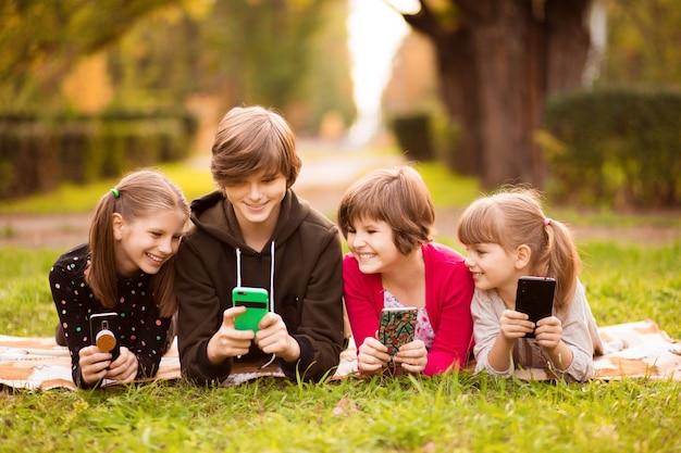 Gruppe von freundinnen, die handys benutzen und zusammen im park plaudern