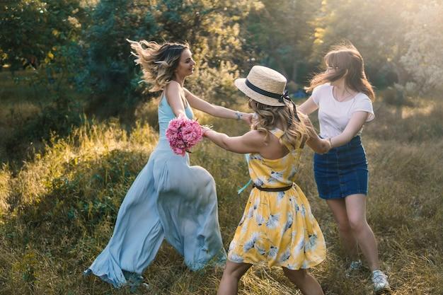 Gruppe von freundinnen, die picknick im freien machen. sie tanzen miteinander revolver. junggesellinnenparty