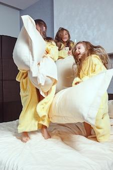 Gruppe von freundinnen, die sich zeit fürs bett nehmen. glückliches lachendes kindergirsl, das auf weißem bett im schlafzimmer spielt