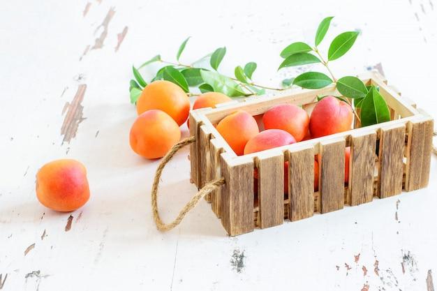 Gruppe von frischen aprikosen mit grünen blättern in der holzkiste