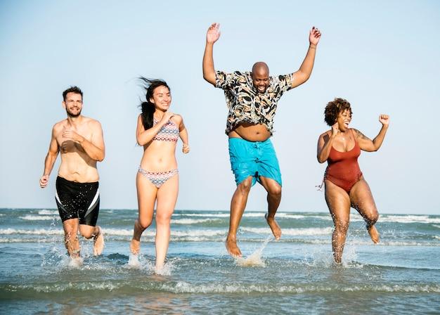 Gruppe von fröhlichen freunden am strand
