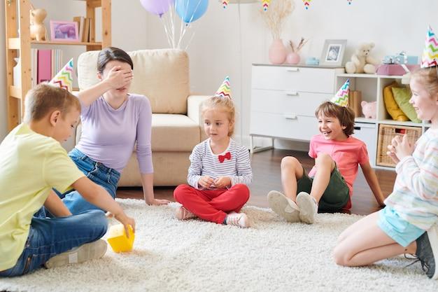 Gruppe von fröhlichen kleinen kindern in geburtstagskappen, die im kreis auf teppich im wohnzimmer sitzen, während sie spiel mit mutter von einem von ihnen spielen