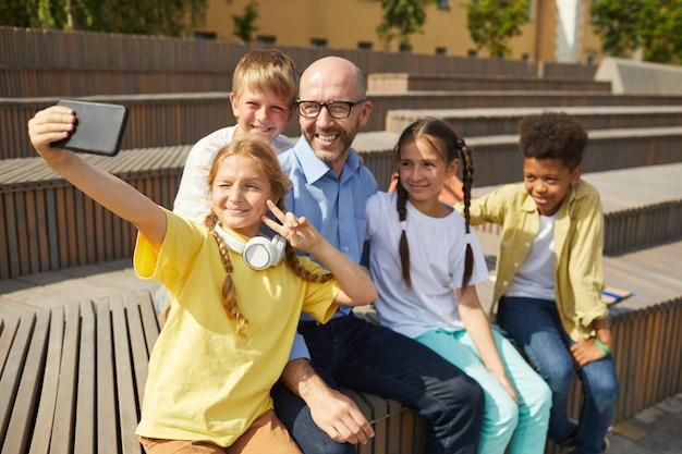 Gruppe von fröhlichen teenager-kindern, die selfie mit lächelndem männlichen lehrer draußen im sonnenlicht nehmen, raum kopieren