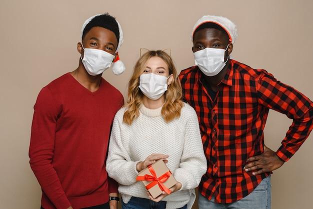 Gruppe von fröhlichen verschiedenen jungen leuten in weihnachtsmannmützen und medizinischen masken, die ein weihnachtsgeschenk halten und die kamera betrachten.