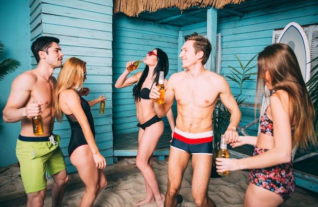 Gruppe von fünf freunden, die in ihrem sommerstrandhaus feiern