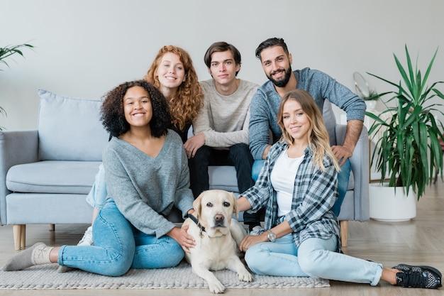 Gruppe von fünf liebevollen jungen und mädchen im teenageralter und weißem labrador, die auf dem boden und auf der couch sitzen