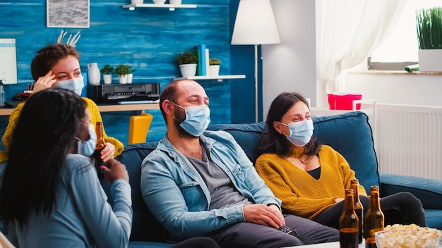 Gruppe von gemischtrassigen freunden, die comedy-shows im fernsehen sehen und lachen und genießen, zeit zusammen mit gesichtsmaske zu verbringen, um eine infektion mit covid 19 während der globalen pandemie zu verhindern und spaß auf der couch zu haben