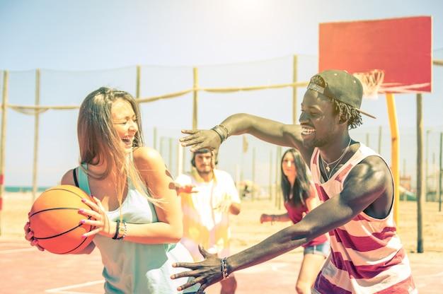 Gruppe von gemischtrassigen glücklichen teenagern, die im freien basketball spielen - kaukasier und schwarze - konzept über sommerferien, sport, spiele und freundschaft
