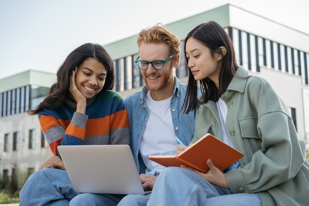 Gruppe von gemischtrassigen studenten, die laptop-prüfungsvorbereitung verwenden