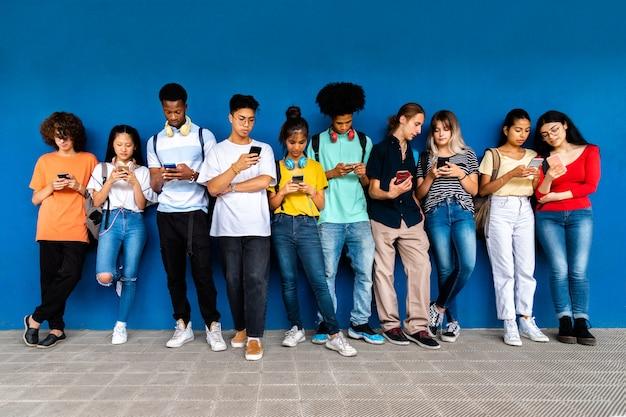 Gruppe von gemischtrassigen teenager-high-school-studenten stehen an der blauen wand gelehnt und schauen auf das handy. konzept für die sucht nach sozialen medien. bildungskonzept.
