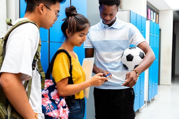 Gruppe von gemischtrassigen teenager-studenten mit smartphone im highschool-korridor. zurück zum schulkonzept. technologiekonzept.