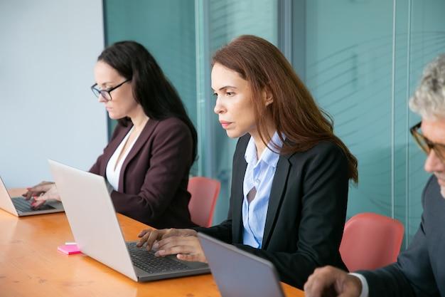 Gruppe von geschäftskollegen, die in der schlange sitzen und computer im büro benutzen. geschäftsleute, die an einem tisch sitzen und auf laptoptastaturen tippen. mittlerer schuss. kommunikations- oder funktechnologie