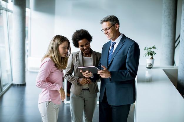 Gruppe von geschäftsleuten, die digitales tablet beim treffen im büro verwenden