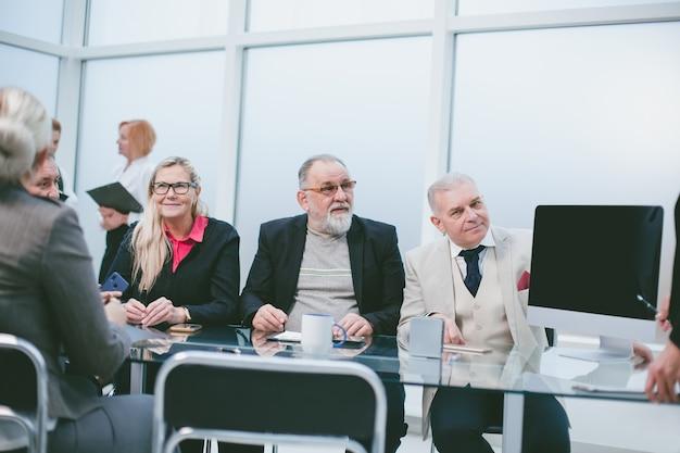 Gruppe von geschäftsleuten, die im konferenzraum am verhandlungstisch sitzen. treffen und partnerschaften