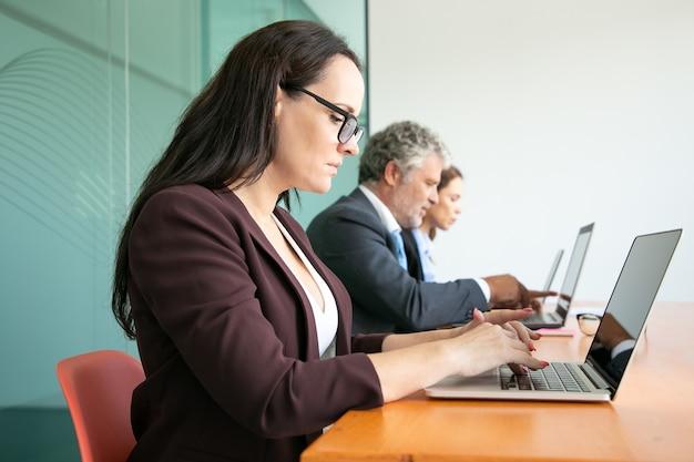 Gruppe von geschäftsleuten, die in der schlange sitzen und computer im büro benutzen. mitarbeiter unterschiedlichen alters tippen auf laptoptastaturen.