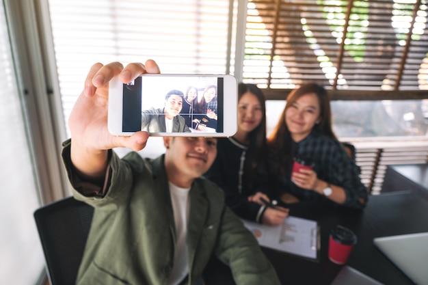 Gruppe von geschäftsleuten, die mit dem handy zusammen ein selfie machen