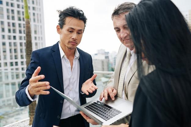 Gruppe von geschäftsleuten, die präsentation auf laptop-bildschirm diskutieren, wenn besprechung auf dem dach des gebäudes