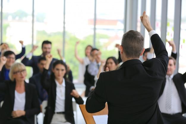 Gruppe von geschäftsleuten in seminar oder meeting durch fokus auf hand erheben