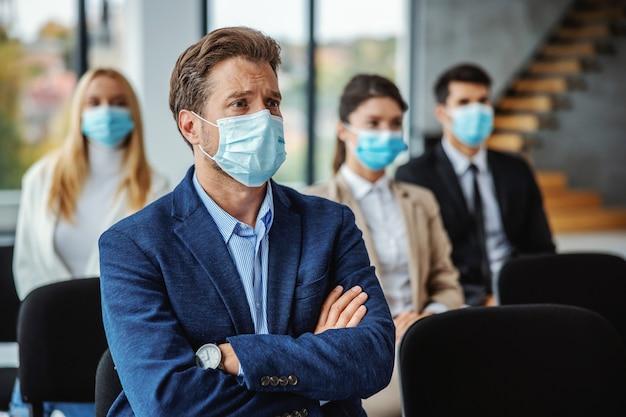 Gruppe von geschäftsleuten mit gesichtsmasken, die während des koronavirus auf einem seminar sitzen. selektiver fokus auf den menschen im vordergrund.