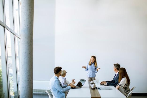 Gruppe von geschäftsleuten mit jungen erwachsenen und älterer kollegin beim treffen im modernen hellen büroinnenraum