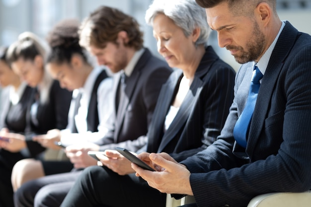 Gruppe von geschäftsleuten mit smartphones, die in einer reihe sitzen.