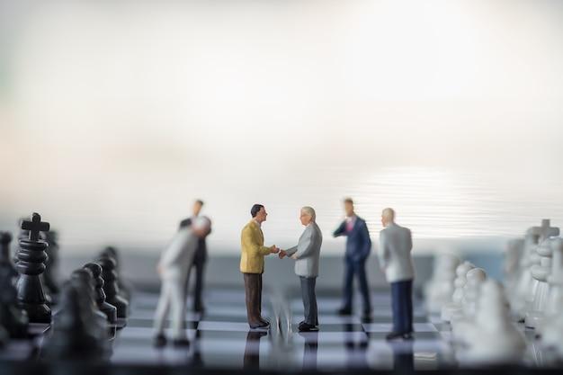 Gruppe von geschäftsmann miniaturfigur menschen treffen auf schachbrett mit schachfiguren