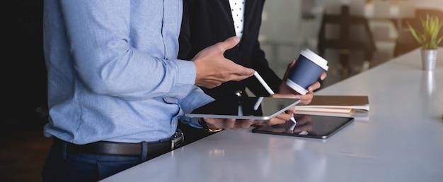 Gruppe von geschäftsmann und buchhalter, die datendokument auf digitalem tablett zur untersuchung des korruptionskontos überprüfen.