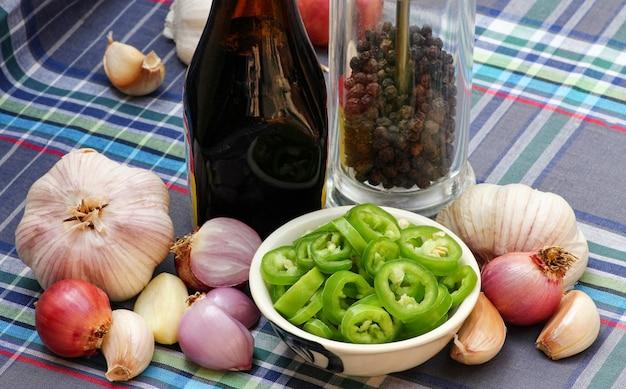 Gruppe von geschnittenen grünen chilis und gewürzen, kräutern, zwiebeln, knoblauch, pfeffer auf dem tisch.