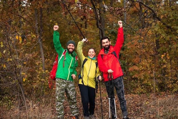 Gruppe von glücklichen abenteurern mit trekkingstöcken, die arme heben und kamera betrachten, während n herbstwald während des gemeinsamen wanderns stehen
