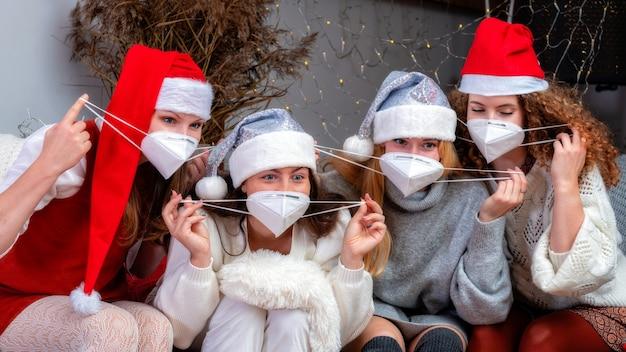 Gruppe von glücklichen frauenmädchen in weihnachtsmützen und gesichtsmasken nehmen ein selbstporträt des feiertags