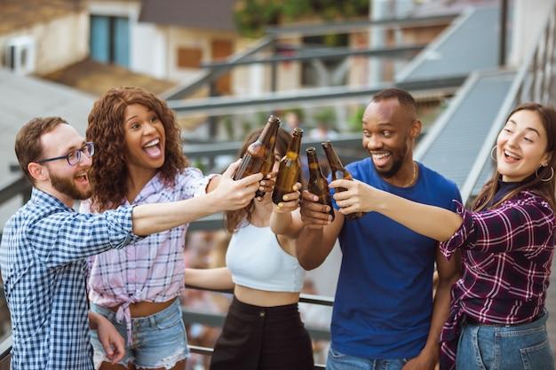 Gruppe von glücklichen freunden, die bierparty im sommertag haben. gemeinsam im freien ausruhen, feiern und entspannen, lachen. sommerlebensstil, freundschaftskonzept.
