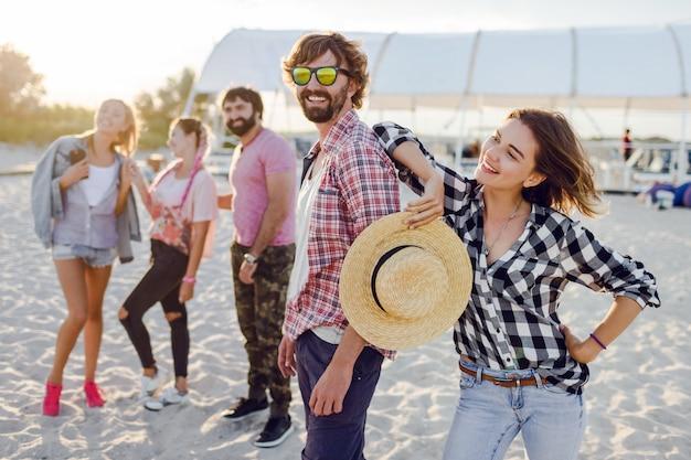 Gruppe von glücklichen freunden, die erstaunliche zeit zusammen verbringen und am sonnigen strand entlang gehen