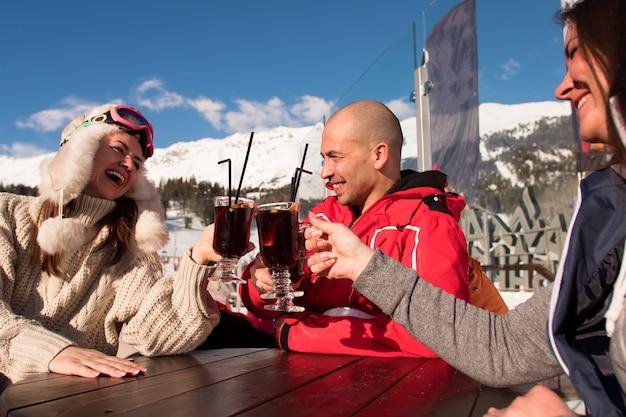 Gruppe von glücklichen freunden, die mit getränk nach skitag im café am skigebiet jubeln.