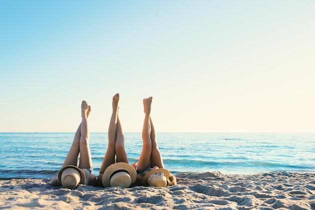 Gruppe von glücklichen freunden, die spaß am ozeanstrand im morgengrauen mit den beinen oben haben