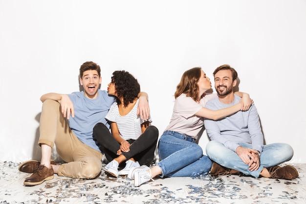 Gruppe von glücklichen gemischtrassigen leuten, die auf einem boden sitzen