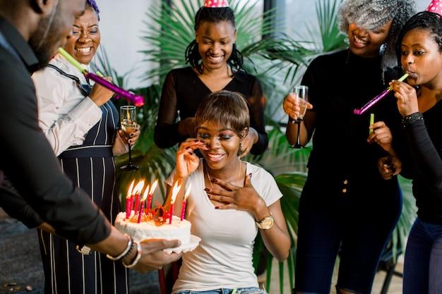 Gruppe von glücklichen jungen afrikanischen leuten, die geburtstag feiern und spaß zusammen haben