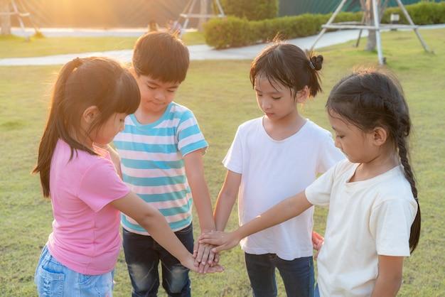 Gruppe von glücklichen jungen asiatischen kindern stapeln oder stapeln hände zusammen draußen im stadtparkspielplatz am sommertag. kinder- und erholungskonzept.