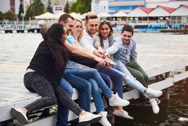 Gruppe von glücklichen jungen freunden auf dem pier, freude am spielen schafft emotionales leben.