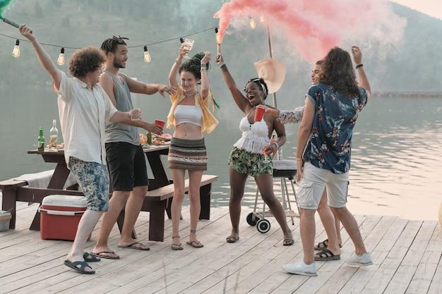 Gruppe von glücklichen jungen leuten, die auf einem pier stehen und spaß haben, den sie sommerfest besuchen