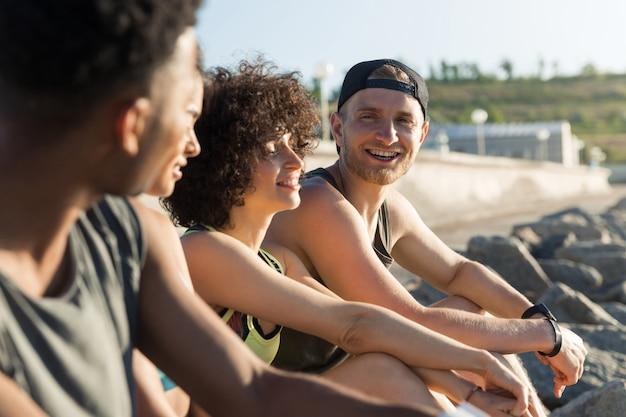 Gruppe von glücklichen jungen leuten in der sportbekleidung, die beim ausruhen sprechen