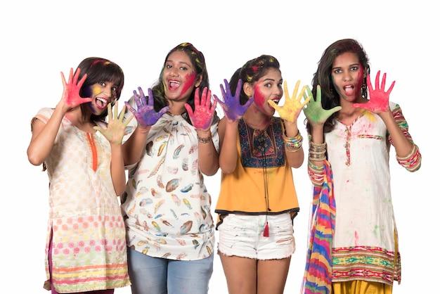 Gruppe von glücklichen jungen mädchen, die spaß mit buntem puder am holi festival der farben haben