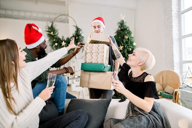 Gruppe von glücklichen jungen vier freunden, die lachen und weihnachtsgeschenke teilen