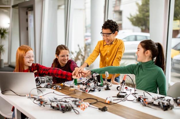 Gruppe von glücklichen kindern, die elektrisches spielzeug und roboter im klassenzimmer der robotik programmieren