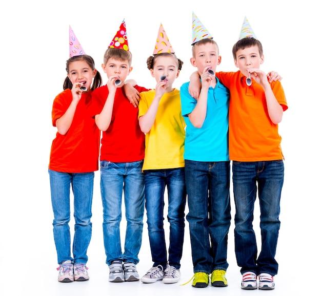 Gruppe von glücklichen kindern in farbigen t-shirts mit partygebläsen - lokalisiert auf einem weißen hintergrund
