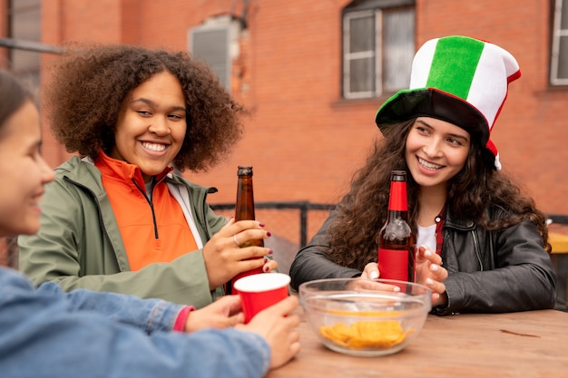 Gruppe von glücklichen mädchen mit bier, die letztes fußballspiel in der städtischen umgebung diskutieren